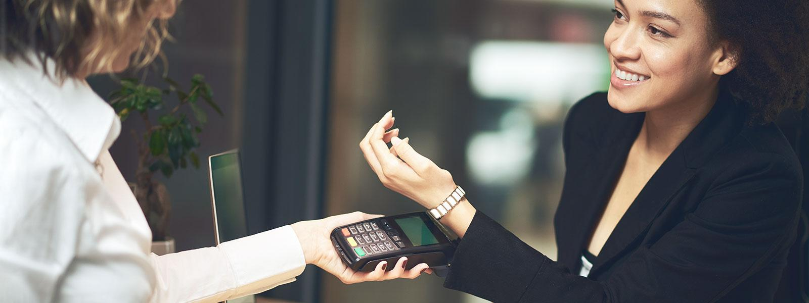 woman makes contactless payment with wearable payment technology (wristband)